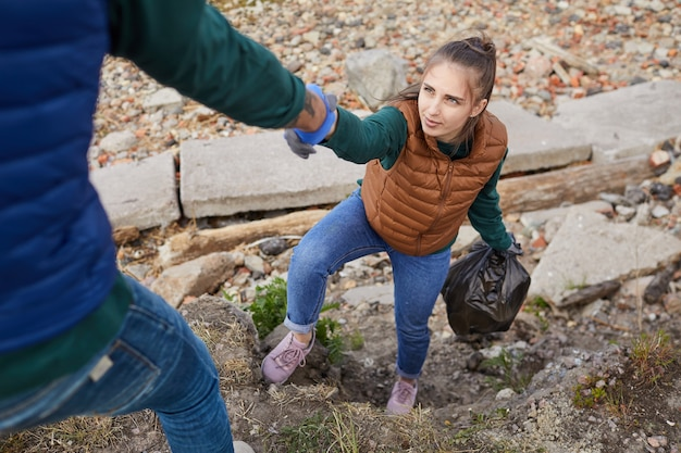 Man helping young woman up while they picking up garbage outdoors