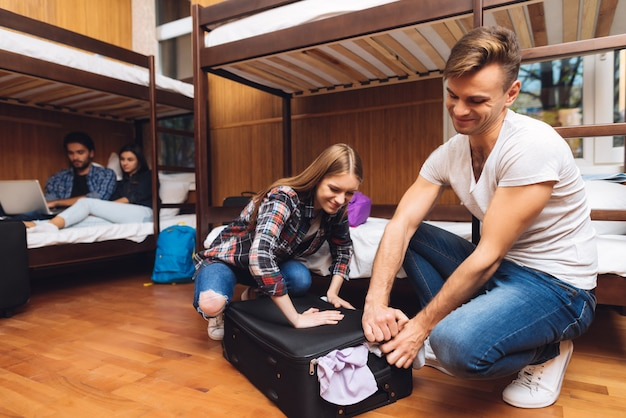 Man helps girl stack things and close valise.