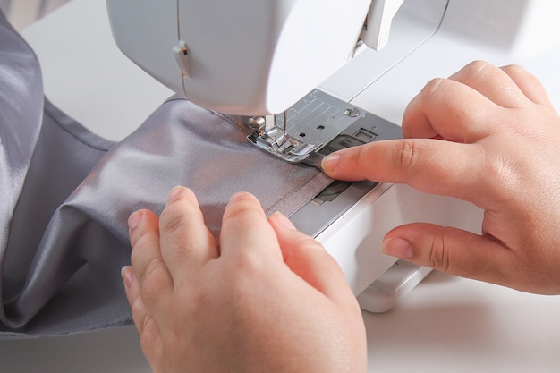 Man hem a curtain on a sewing machine. sewing, hobbies, hobby, home improvement.