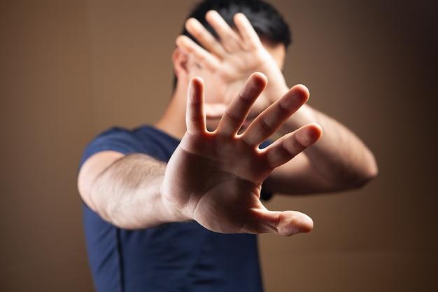 男は手で顔を隠す