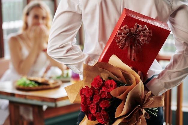 여자 친구를위한 생일 선물로 등 뒤에 장미 꽃다발과 선물 상자를 숨기는 남자