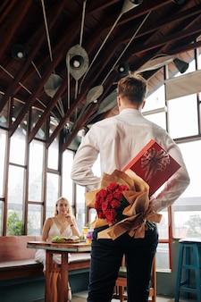 Мужчина прячет за спиной коробку шоколада и букет цветов для подруги