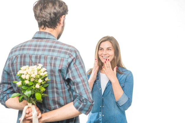 Man hiding flower behind his back in front of happy girlfriend