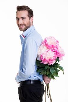 L'uomo nasconde un fiore dietro la schiena isolato su sfondo bianco.