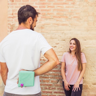 Man hiding gift from his happy girlfriend behind back