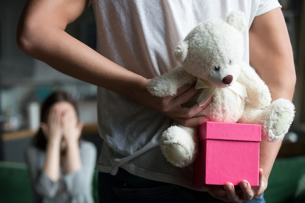 Man hiding gift making romantic surprise for wife, rear closeup