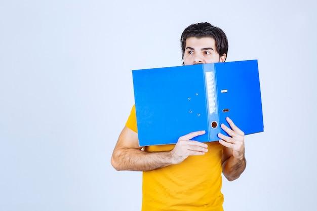 파란색 폴더 뒤에 그녀의 얼굴을 숨기는 남자.