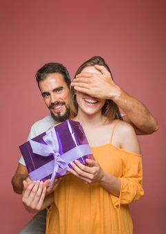Man hiding her girlfriend's eye holding gift box against colored background