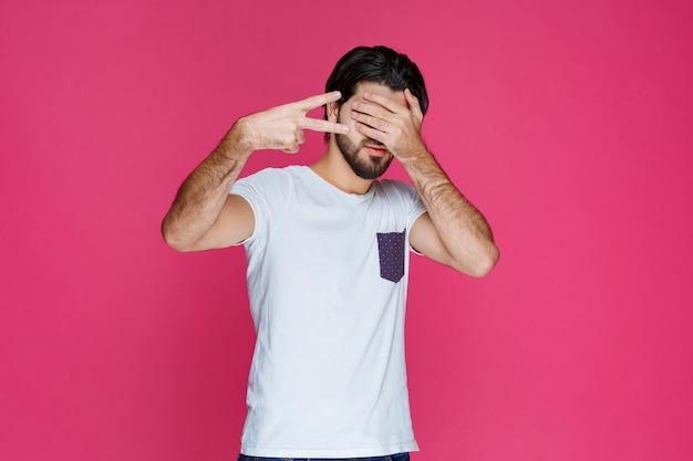 L'uomo nasconde il viso dietro le mani.