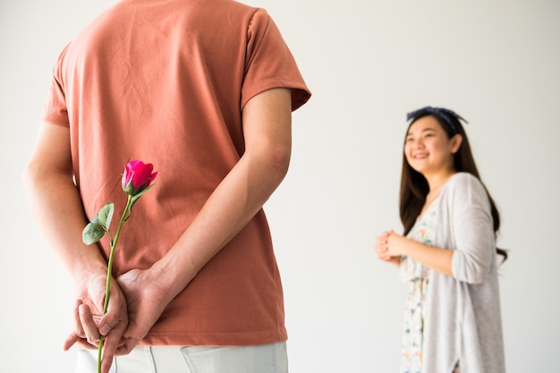 Man hiding pink rose flower to surprise his girlfriend in valentine's day. smilling asian woman look at his boyfriend with copy space for text.