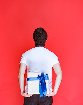 Man hiding a white gift box behind himself to make a surprize.