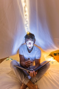 Man highlights his face with flashlight sitting under the curtain on bed holding album