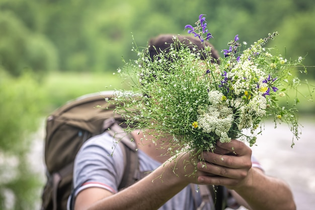 A man on a hike holds a bouquet of wildflowers