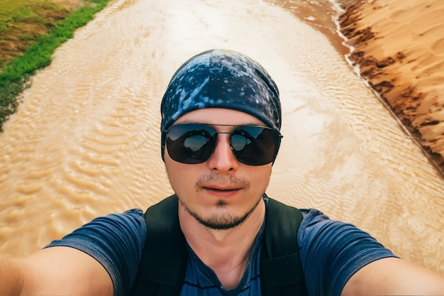 Man on a hike with a backpack takes a selfie on camera face in sunglasses and a bandana while traveling