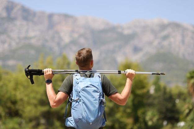 男のハイカーは、山のハイキングと健康の概念の頂点にフィンランドの杖を持っています