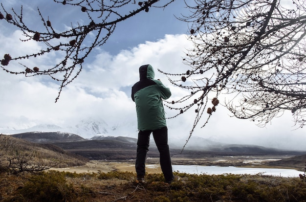Man hiker looks at a beautiful mountain valley in the mountains in winter in fog. cold weather travel and out-of-town concept