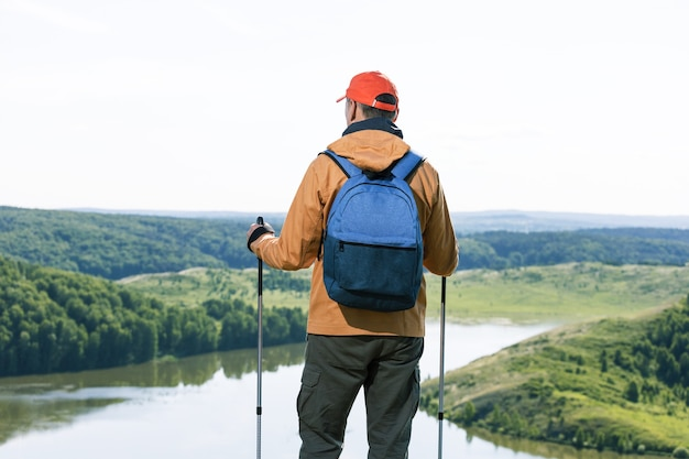 Man hiker observing the the green valley with lake and thinking. travel lifestyle wanderlust adventure concept summer vacations outdoor.