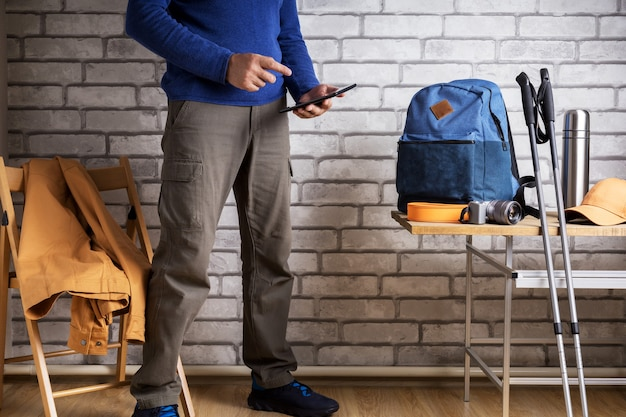 ホテルの部屋や自宅でデジタルタブレットを使って旅行を計画している男性ハイカー。観光旅行者計画ルート。