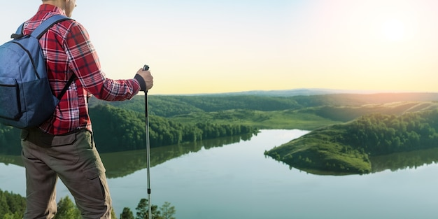 Man hiker standing on a ledge of a mountain, enjoying the beautiful sunset. hiking, freedom outdoor trip in summer.