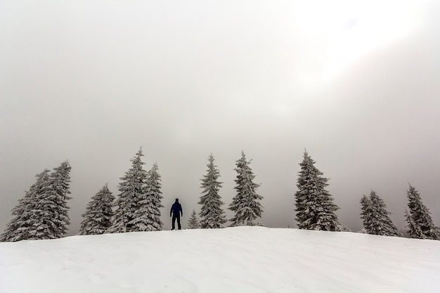 Man hiker standing in winter snow covered mountains enjoying view