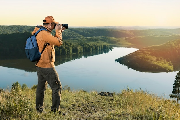 Man hiker in a vibrant yellow coat with a backpack and camera taking photo of sunset mountains. travel lifestyle hobby concept adventure active vacations outdoor.