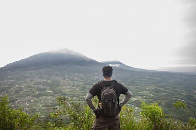 산 꼭대기에 배낭을 가진 남자 등산객, 동기 부여와 목표 달성의 개념