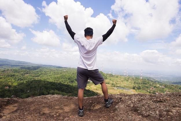 Путешественник человек с рюкзаком на вершине горы обратно, концепция мотивации и достижения цели