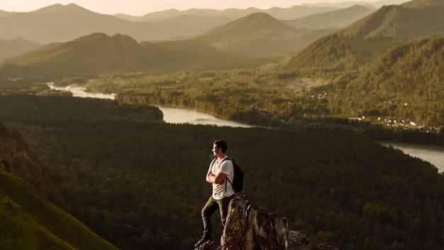 휴가에 산 꼭대기에서 계곡의 전망을 즐기는 배낭과 남자 등산객. 산 여행 및 모험 개념