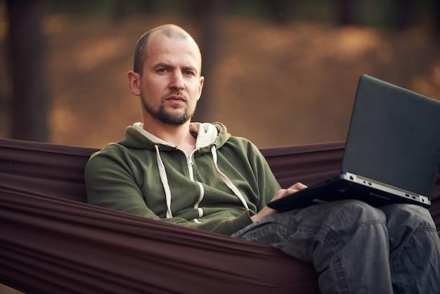 Человек hiker работает на ноутбуке в гамаке в сосновом лесу. концепция удаленной работы