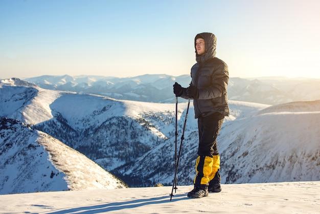 일몰에 눈 덮인 산의 정상에 서있는 남자 등산객