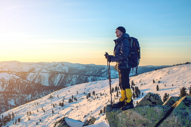 Man hikers standing on snowy mountain peak at sunset