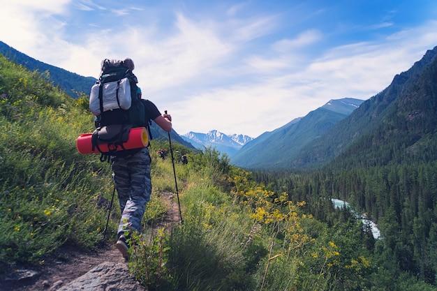 重いバックパックで日没の山でハイキングする男旅行ライフスタイル放浪癖冒険コンセプト夏休み屋外一人で野生に。ノルディックウォーキングスティック。