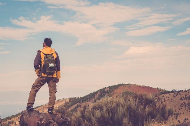 軽いバックパックで日没の山でハイキングする男