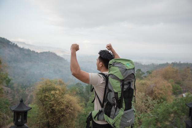 自然の中でハイキングする男は彼の腕を上げる