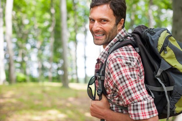 森の中をハイキングする男