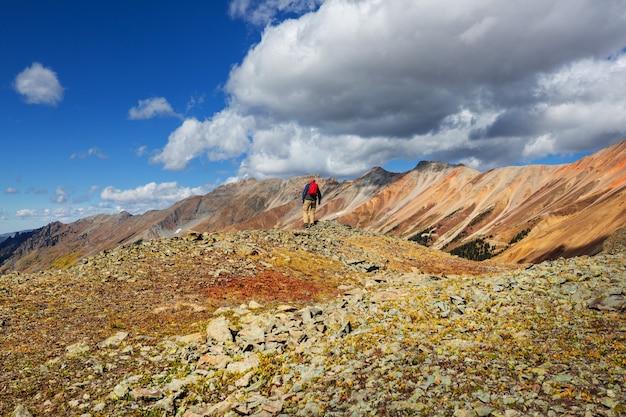 秋のシーズンにコロラド州ロッキー山脈でハイキングする男性