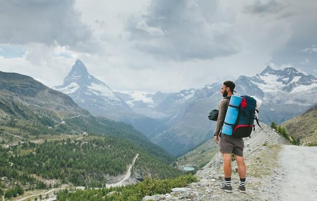 Man hiking to matterhorn mountain in summer in zermatt city region, switzerland