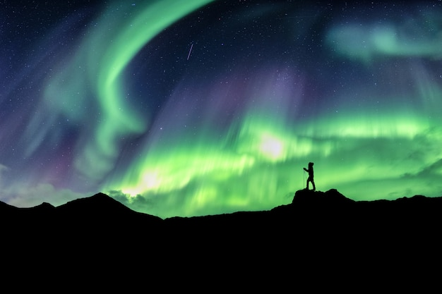 Man hiking on mountain with northern lights explosion