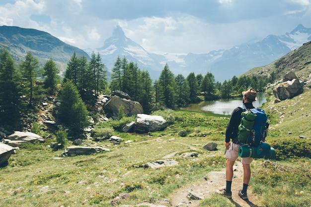 Человек, идущий на гору маттерхорн с белым снегом и голубым небом в городе церматт в швейцарии.