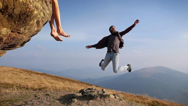 青い空の山にジャンプする男のヒップスター