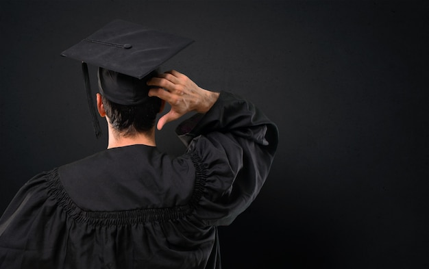 Man on his graduation day university on back position looking back while scratching head