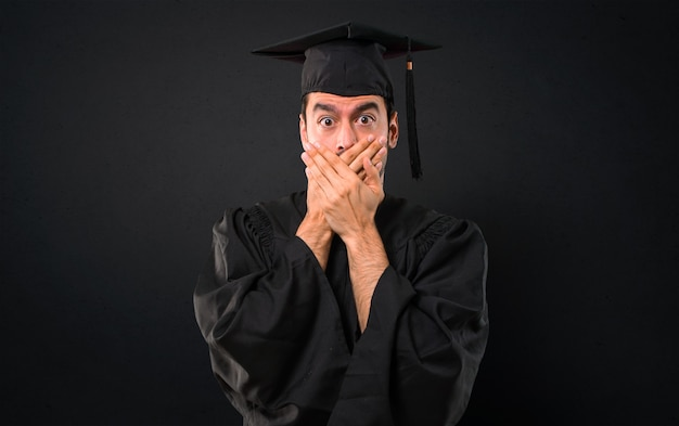 Man on his graduation day university covering mouth with both hands for saying something