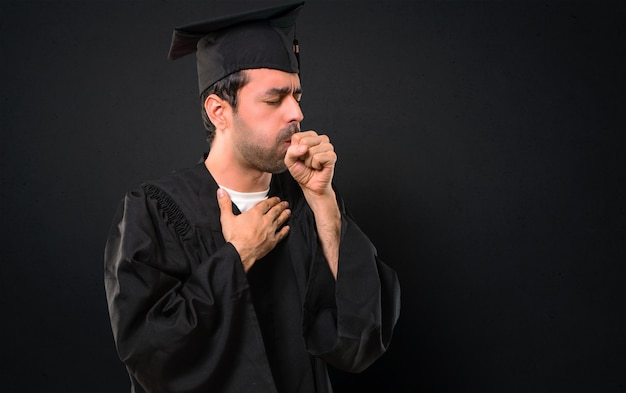 Man on his graduation day university is suffering with cough and feeling bad on black background