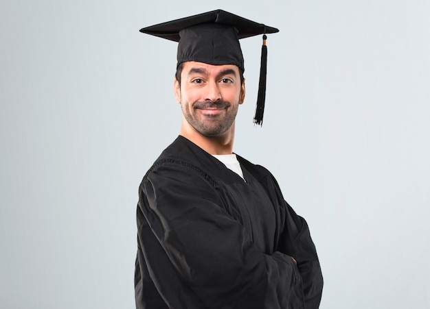 Man on his graduation day university keeping the arms crossed in lateral position while sm
