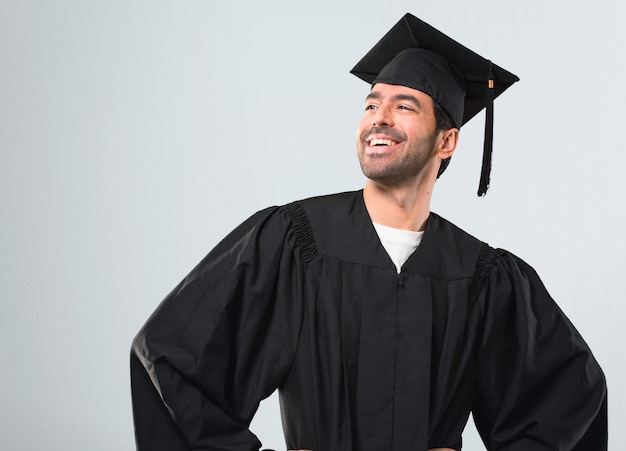 Man on his graduation day university posing with arms at hip and laughing on grey background