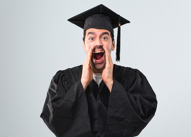 Man on his graduation day university shouting with mouth wide open and announcing somethin