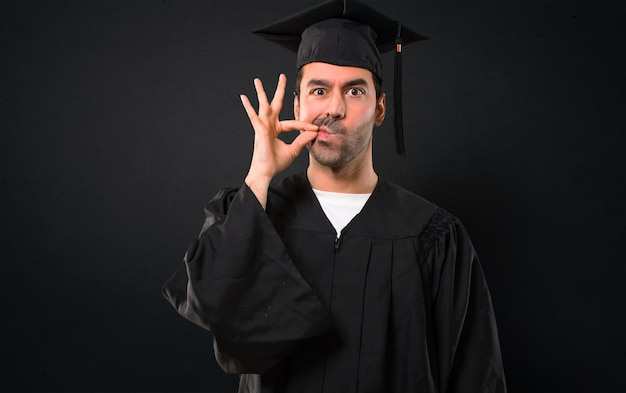 Man on his graduation day university showing a sign of closing mouth and silence gesture