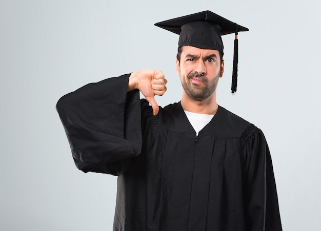 Man on his graduation day university showing thumb down sign with negative expression