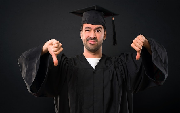 Man on his graduation day university showing thumb down with both hands