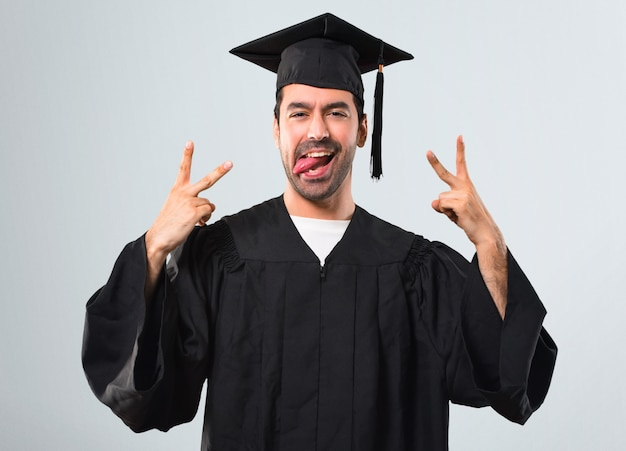 Man on his graduation day university showing tongue at the camera having funny look